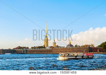 ST PETERSBURG RUSSIA-OCTOBER 3 2016. St Petersburg panorama - Peter and Paul fortress at Hare island with touristic sailboat at Neva river in St Petersburg Russia