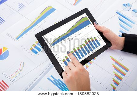 Close-up Of Businesswoman Analyzing Financial Graphs Using Digital Tablet On Desk