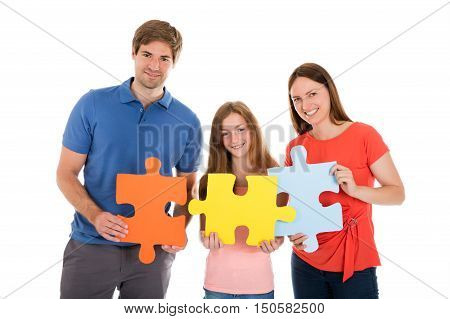 Portrait Of A Happy Family Holding Jigsaw Puzzle Pieces