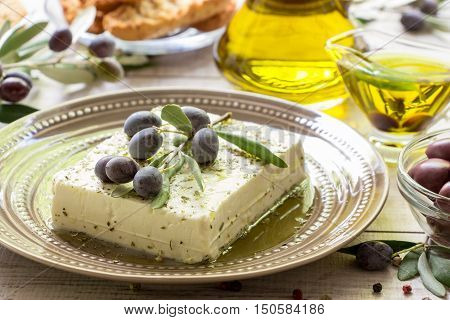 Feta cheese in the plate near olives, olive oil, crackers, branches of olive tree on a light white wooden background. Feta cheese and olive branch. Horizontal. Daylight. Close.