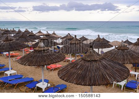 Tropical thatch umbrellas on an deserted beach in a nasty weather on Lefkada island Greece.