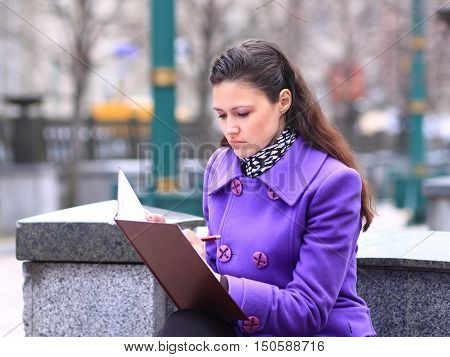 girl student with  the syllabus on the street in autumn day