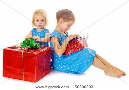 Two charming little girls , sisters, in identical blue dresses with polka dots. Girl looking at gifts Packed in beautiful red paper tied with a bow.Isolated on white.