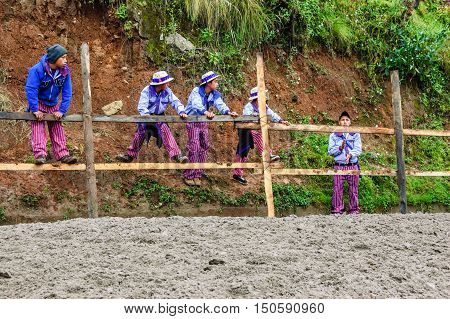 Todos Santos Cuchumatan, Guatemala - November 1 2011: Boys in Todos Santos traditional costume watch All Saints' Day horse race in highland town of Todos Santos, Huehuetenango