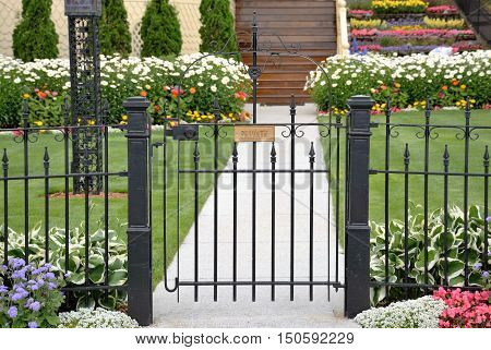 A cast iron gate keeps the public out of a private yard.