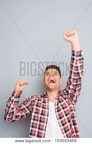 Yes! Successful Young Man Triumphing With Raised Fists