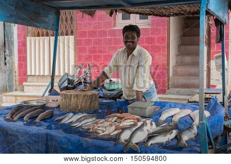 Madurai India - October 21 2013: A fish merchant displayed plenty of large fishes on blue carpet and sells them with a big smile out of his stall wheeled onto the street.