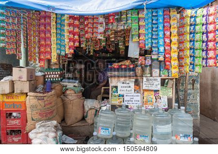 Madurai India - October 21 2013: A small shop sells water jugs beans out of bags and all kinds of cheap merchandise that is packed per single unit.