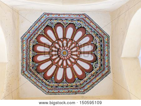 Madurai India - October 21 2013: Shot on the abundant decoration of one octagon ceiling at Nayak Palace. Cream with wine-colored lotus images and green blue yellow backgrounds.