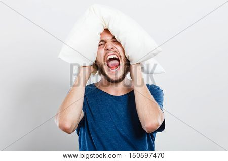 Stressful unpleasant situation conflict. Angry mad young man closing ears with pillow protecting from loud noise. Guy not wanting to listen or can not fall asleep