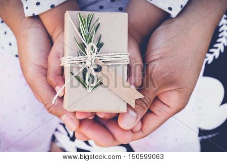 Parents And Child Holding Eco Gift Box With Brown Tag, Toning Background