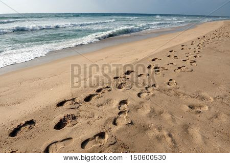 Many footsteps in a row along the sand on a beach.