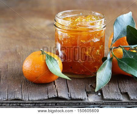 citrus mandarin jam in a glass jar on a wooden table