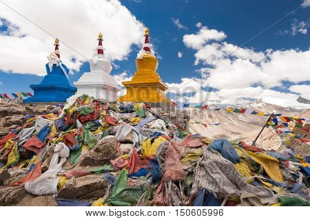 Three buddhist stupa with Buddhist prayer flags with blue sky at Khardongla pass, Leh, Ladakh, India.
