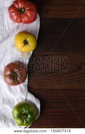 Top view of heirloom tomatoes on a kitchen towel and dark wood table.