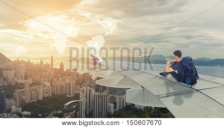Man traveler sit on wing of airplane with touchscreen on mobile for connection to world travel map.