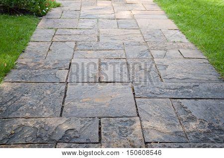 close up cement block way in nature garden