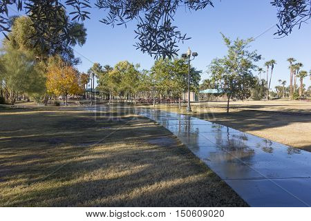 Wet walkway among shady green trees in Phoenix downtown Encanto park Arizona
