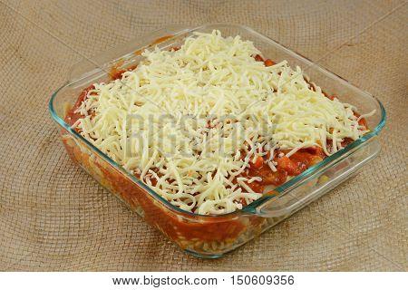 Unbaked prepared casserole dish with turkey, mixed vegetables, pasta, marinara sauce and shredded mozzarella cheese