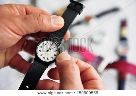 Man hands adjusting the time on a watch. Concept photo of Daylight saving, time alarm travel and changing time zone.