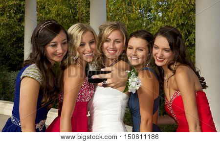 Beautiful Teenage Girls at the Prom.  They are taking a selfie with a cell phone.
