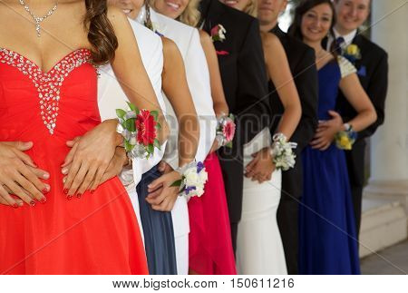 Group of Teenagers At the Prom - They are lined up in a row with the focus on their hands and corsages.