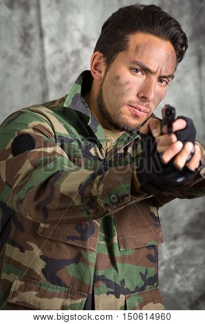 portrait of soldier militar latin man in camouflage uniform pointing a gun to the front