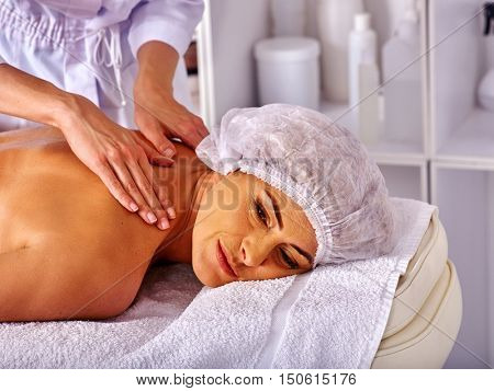 Woman middle-aged take back massage in spa salon with young beautician. A lot of bottle on backgriund.
