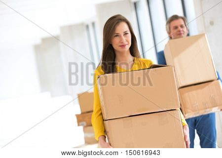 Young businesswoman with male colleague carrying cardboard boxes in new office