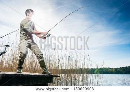 Fisherman catching fish angling at the lake under a blue sky