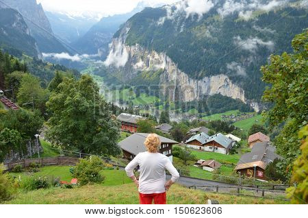 Woman looking at mountains and valley view. Tourist  woman looking forward on mountain landscape background. Senior woman standing admiring a mountaintop view. Travel concept. Switzerland.
