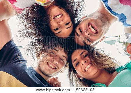 Close up of young happy people with their heads together having fun in a summer party. Young people lifestyle concept. View from below.