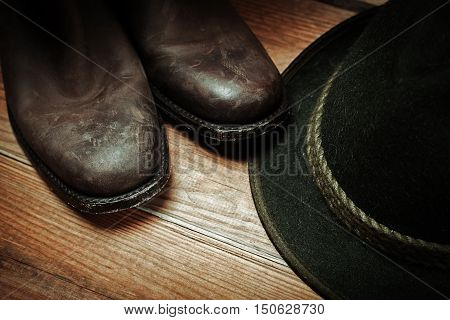 American West rodeo cowboy dirty and used brown botts and hat