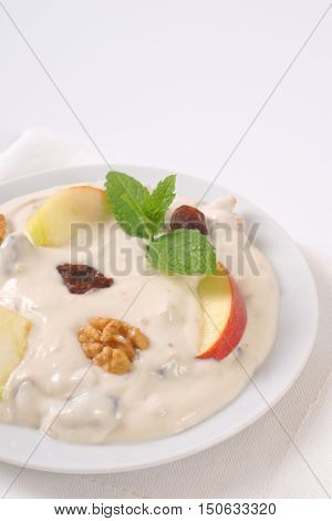 plate of cream cheese with apples, nuts and raisins on white place mat