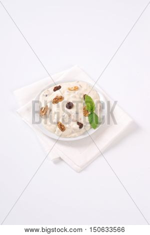 plate of cream cheese with nuts and raisins on white place mat