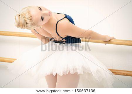 Close-up portrait of a beautiful ballet dancer training near the ballet barre in a ballet class.