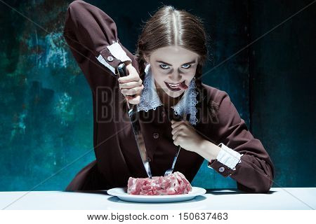 Portrait of a young girl with knife fork and and a piece of raw meat on a plate. Girl in school uniform as killer. The image in the style of Halloween and Addams family