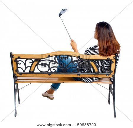 Back view of a woman to make a selfie stick portrait sitting on the bench. girl watching. Rear view people collection. backside view of person. Isolated over white background. Brunette sitting on the