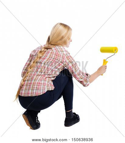 Back view of a girl who paints the paint roller. rear view people collection. backside view of person. Isolated over white background. Squatting woman paints the wall roller.