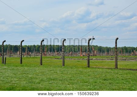 OSWIECIM POLAND - MAY 12 2016: Ruins of concentration camp Auschwitz Birkenau II behind the fence of barbed wire in Brzezinka Poland.