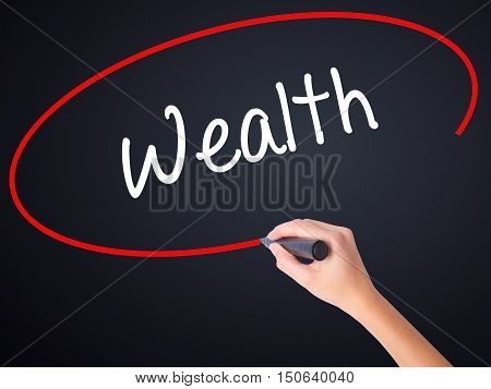 Woman Hand Writing Wealth With A Marker Over Transparent Board