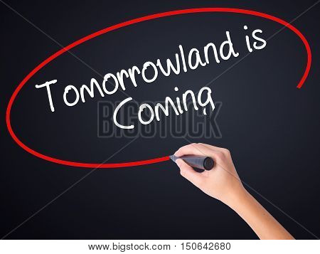 Woman Hand Writing Tomorrowland Is Coming With A Marker Over Transparent Board