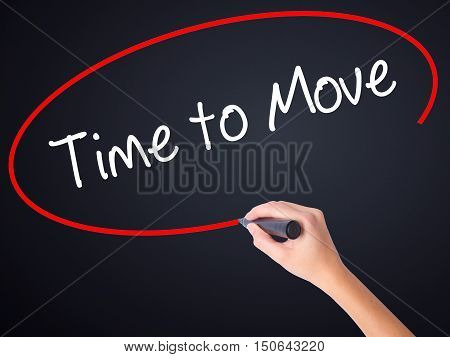Woman Hand Writing Time To Move With A Marker Over Transparent Board