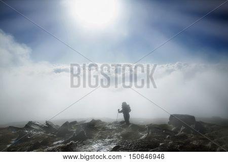 Mountaineer reaches the top of mountain in fog and autumn morning sun. Carpathian Mountains.Ukraine.