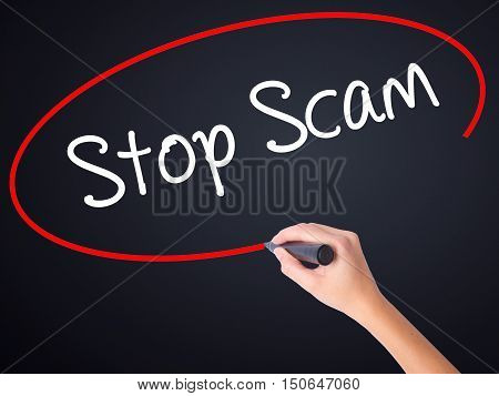 Woman Hand Writing Stop Scam With A Marker Over Transparent Board