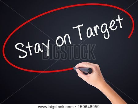 Woman Hand Writing Stay On Target With A Marker Over Transparent Board .