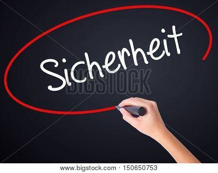 Woman Hand Writing Sicherheit (safety In German) With A Marker Over Transparent Board