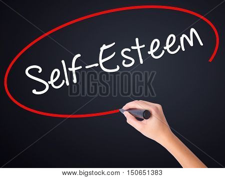 Woman Hand Writing Self-esteem With A Marker Over Transparent Board .