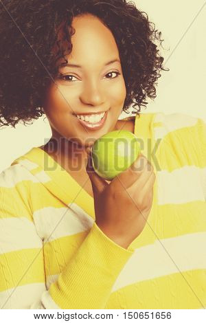 Beautiful smiling black woman eating apple