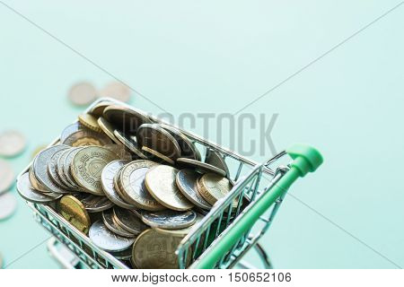 Shopping Cart Full Of Coins Over The Green Background
